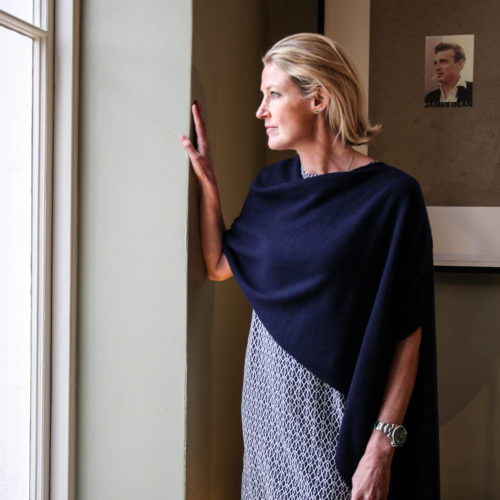 Woman wearing our Cashmere Wing Wrap looking out of a large window